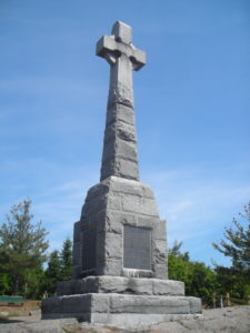 A tall memorial made out of gray stone in the shape of a cross, with a dark gray plaque at the base.